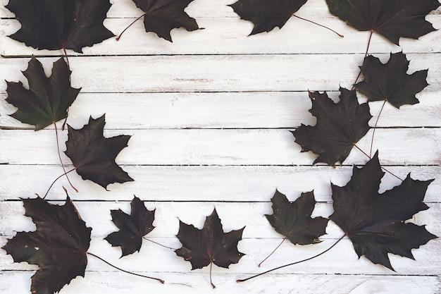 Feuilles d'érable automne sombre sur une planche de bois, blanc. Photo Premium