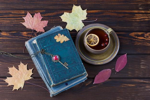 Feuilles d'érable, vieux livres et thé dans une tasse avec du citron Photo Premium