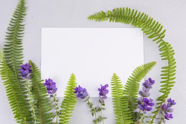 Feuilles de fougère verte avec des fleurs et du papier sur la table Photo gratuit