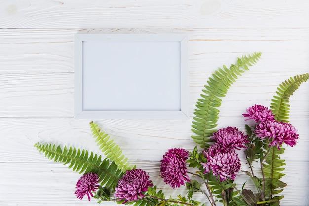 Feuilles de fougère verte à fleurs violettes et cadre sur table Photo gratuit