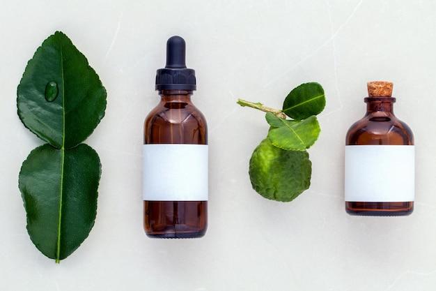 Feuilles de kafir fraîches llime et huiles de soins de santé alternatifs sur fond de marbre. Photo Premium