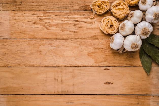 Feuilles de laurier; bulbes d'ail et pâtes crues sur vieux papier peint texturé avec un espace pour le texte Photo gratuit