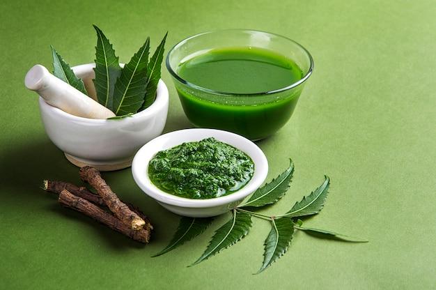 Feuilles de neem médicinales en mortier et pilon avec pâte de neem, jus et brindilles Photo Premium