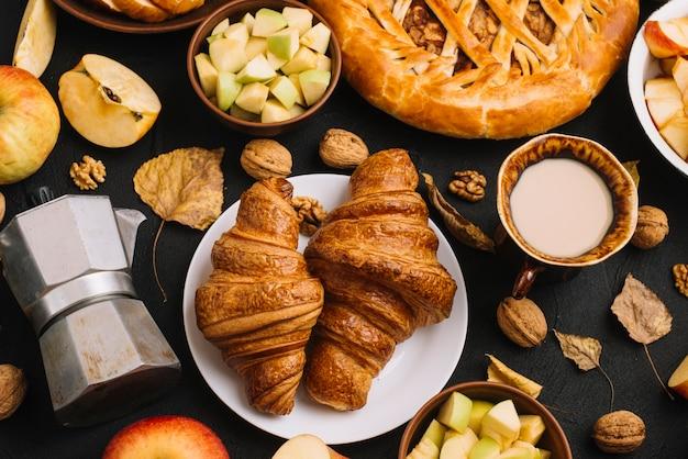 Feuilles et noix au milieu de la pâtisserie et des boissons Photo gratuit