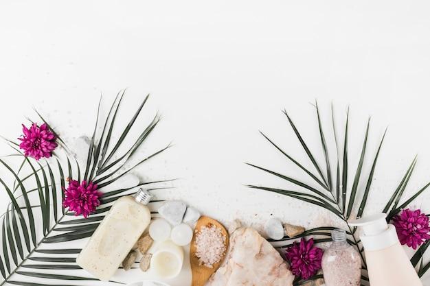 Feuilles de palmier; fleur; gommage corporel; sel; pierres de spa sur fond blanc Photo gratuit