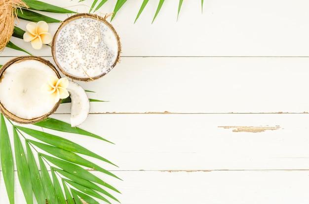 Feuilles de palmier vert avec des noix de coco sur une table en bois Photo gratuit