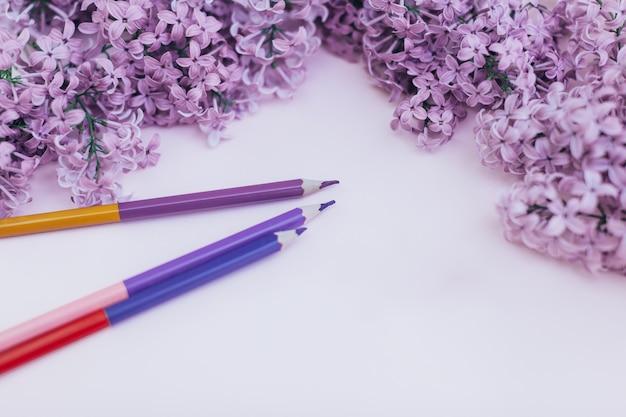 Feuilles de papier blanc et lilas de fleurs printanières, sur un fond de couleur. Photo Premium