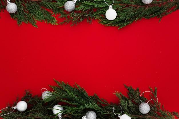 Feuilles de pin de noël sur fond rouge avec une note vide Photo gratuit