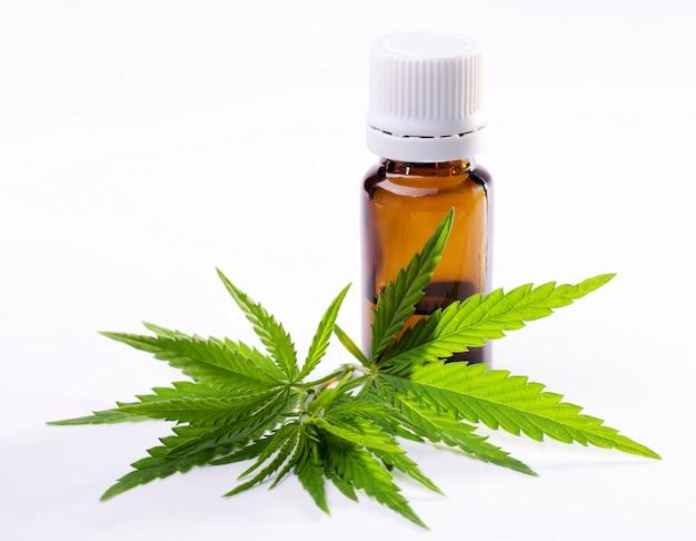 Les feuilles de la plante de cannabis et l'huile d'extrait de cannabis dans la bouteille. Photo Premium