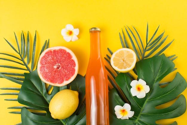 Feuilles de plantes tropicales vertes et bouteille de boisson Photo gratuit