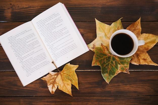 Feuilles près du livre et une tasse de café Photo gratuit