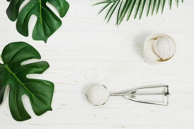 Feuilles près de la tasse et une cuillère de glace Photo gratuit