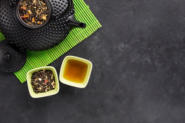 Feuilles séchées et pétales de fleurs pour un thé sain sur un napperon vert Photo gratuit