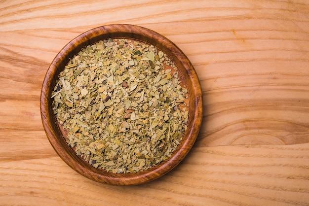 Feuilles de thé sec vert aromatique sur plaque sur fond en bois Photo gratuit