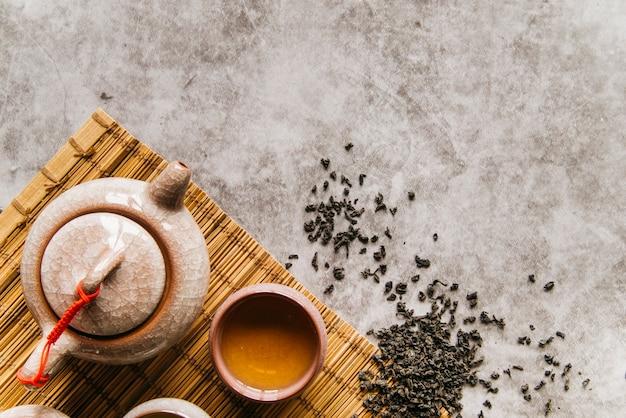 Feuilles de thé séchées avec théière et bol sur napperon sur le fond en béton Photo gratuit