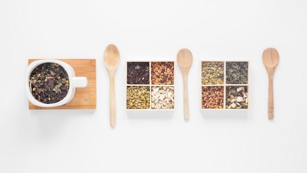 Feuilles de thé sèches; herbes et cuillère en bois disposées dans une rangée sur fond blanc Photo gratuit