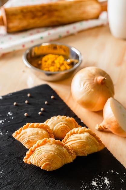 Feuilleté Au Curry Sur Une Assiette Sombre Et Ingrédients Photo Premium