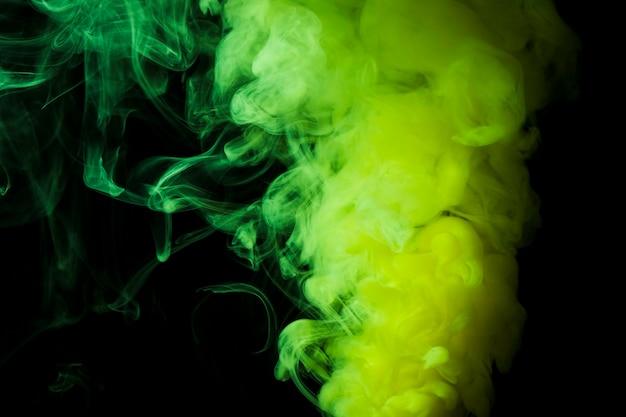 Feuilletés denses de fumée verte sur fond noir Photo gratuit