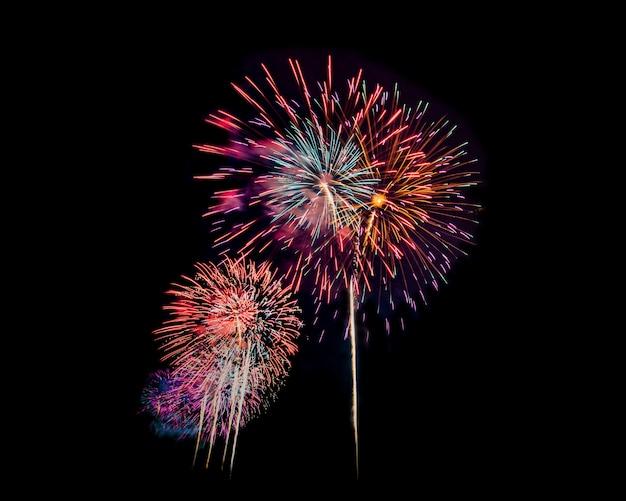 Feux d'artifice la nuit isolés sur ciel sombre pour célébrer le réveillon du nouvel an et une occasion spéciale en vacances Photo Premium