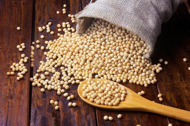 Fèves de soja crues et fraîches dans un sac en tissu rustique sur une table en bois Photo Premium
