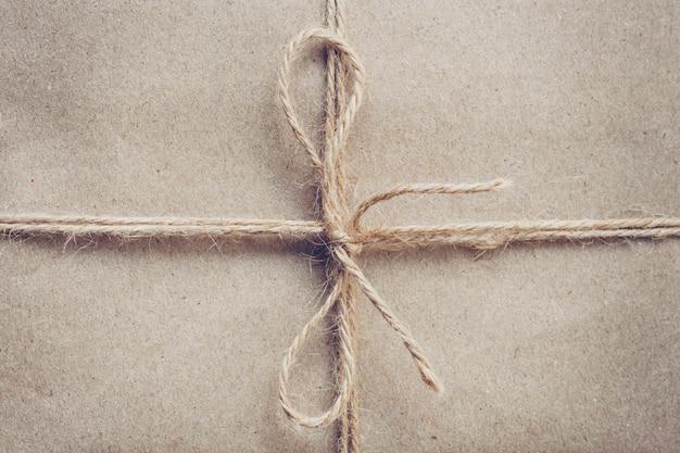 Ficelle ou ficelle attachée dans un arc sur la texture du papier kraft brun. Photo Premium