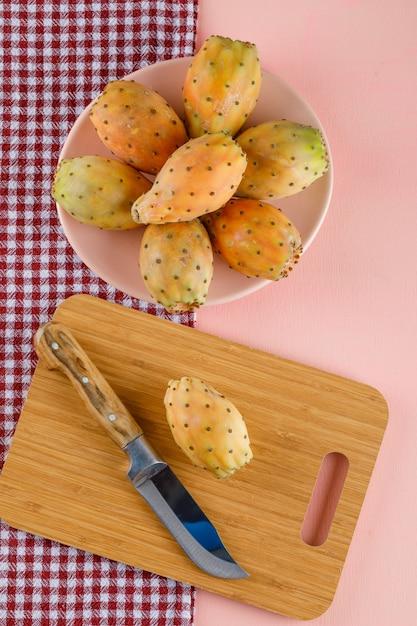 Figues De Barbarie Dans Une Assiette Avec Planche à Découper Et Couteau Sur Tissu De Pique-nique Photo gratuit