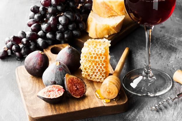 Figues, raisins, pain, miel et vin rouge Photo Premium