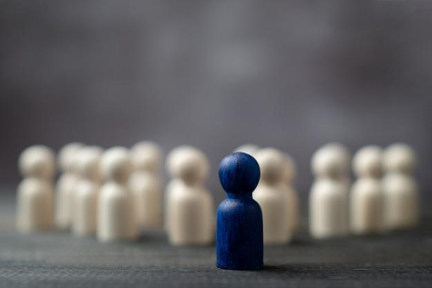 Figure En Bois Debout Devant L'équipe Pour Montrer Son Influence Et Son Autonomisation. Photo Premium