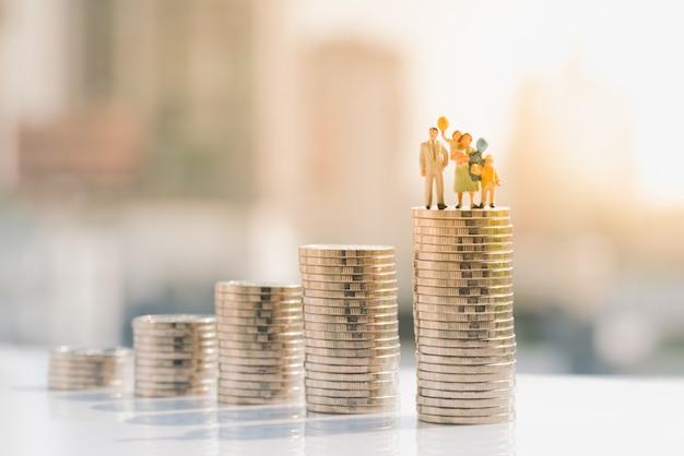 Figure de famille debout sur la pile de pièces de monnaie. Photo Premium