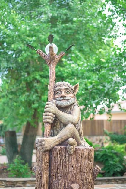 La figure d'un nain avec un bâton de dessin animé dans le parc. fermer Photo Premium