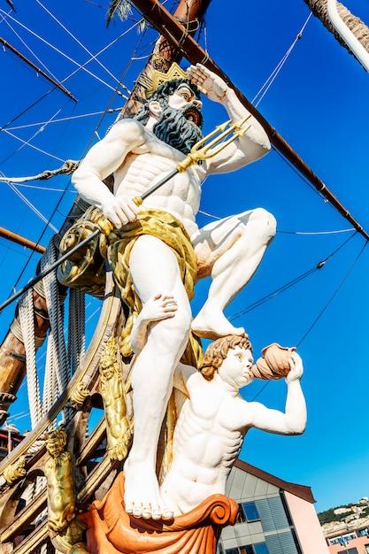 La figure de neptune sur un vieux bateau dans le port contre le ciel bleu. fermer. verticale. Photo Premium