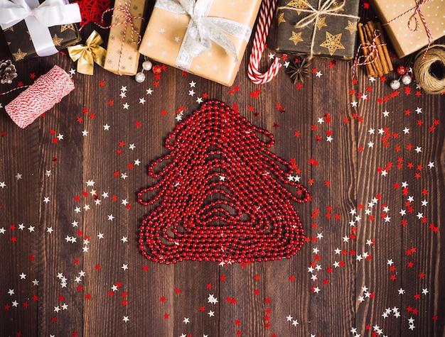 Figure de sapin de noël faite de boîte de cadeau de vacances de perles rouges nouvel an sur la table de fête décorée Photo gratuit