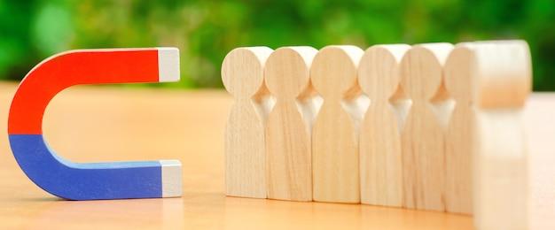 Figures en bois de personnes et un aimant. Photo Premium