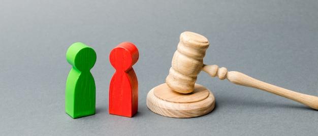 Figures En Bois De Personnes Debout Près Du Marteau Du Juge. Litige. Rivaux D'affaires. Photo Premium