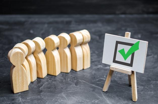 Des figures humaines en bois se tiennent ensemble à côté d'une coche dans la case. le concept d'élections Photo Premium
