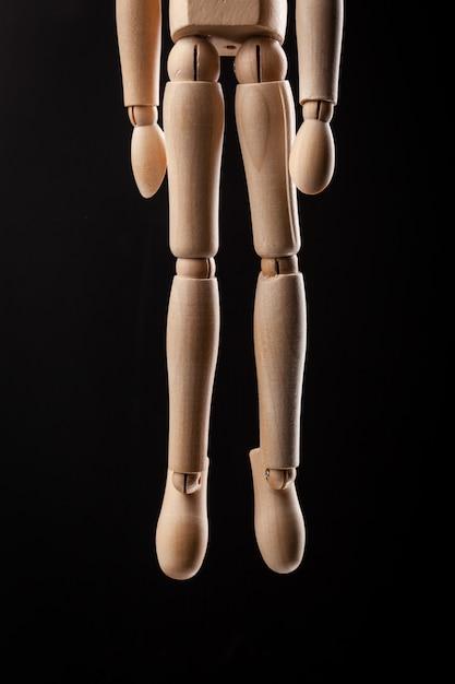 Figurine En Bois Pendue à Une Corde Isolée Sur Fond Noir Photo Premium