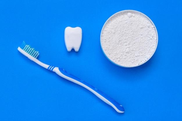 La Figurine De Dent Sourit à Côté De La Poudre à Dents Et De La Brosse à Dents. Mise à Plat. Photo Premium