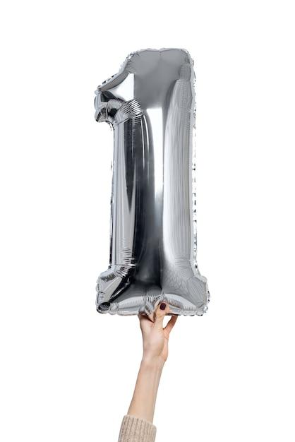 Figurine Gonflable Argentée Une Dans Les Mains D'une Femme. Fermer. Isoler Sur Fond Blanc. Photo Premium
