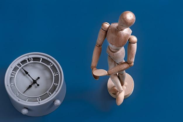 La Figurine D'homme En Bois Sur Un Mur Bleu. Photo gratuit