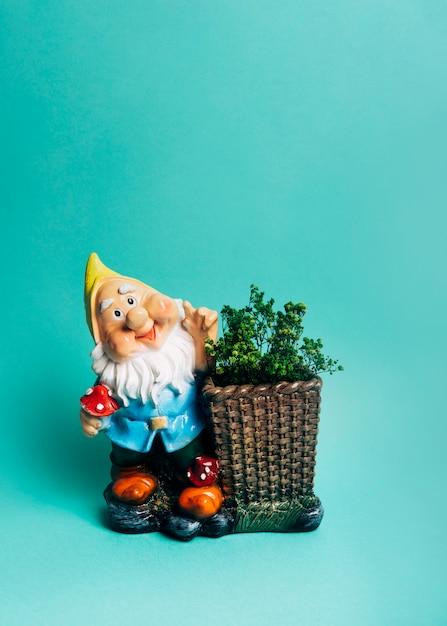 Figurine naine avec spectacle dans le panier contre fond coloré Photo gratuit