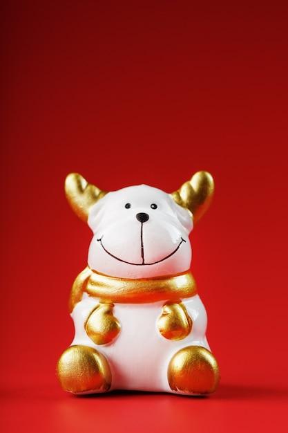 Figurine De Vache De Noël Sur Un Mur Rouge. Symbole De La Nouvelle Année Du Taureau 2021. Isoler Photo Premium