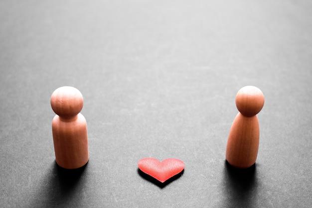 Figurines En Bois Représentant Un Couple D'homme Et De Femme Amoureux, Avec Un Beau Coeur Rouge, Isolé Sur Fond Noir. Photo Premium