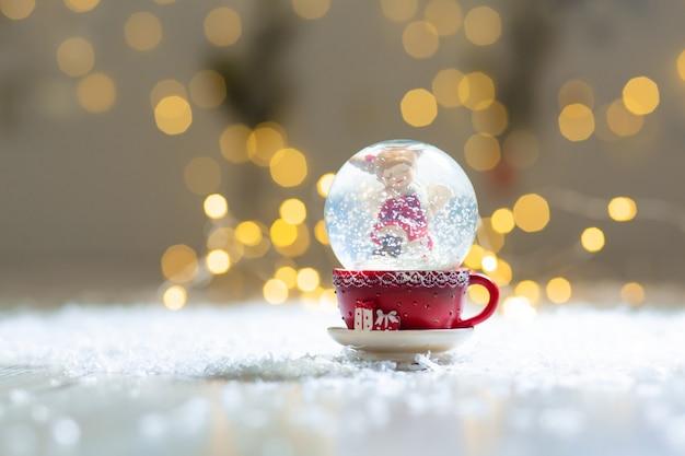 Figurines Décoratives D'un Thème De Noël. Boule De Verre Avec Des Flocons De Neige, à L'intérieur De Laquelle Se Trouve Un Ange De Noël. Photo Premium