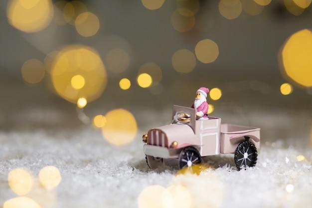 Figurines Décoratives D'un Thème De Noël. La Statuette Du Père Noël Monte Sur Une Voiture Miniature Avec Une Remorque Pour Cadeaux. Photo Premium
