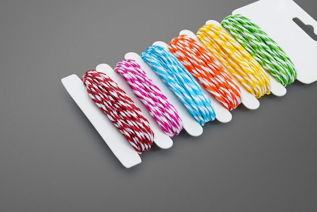 Fil coloré sur fond gris. modèle de corde de couleurs. Photo Premium