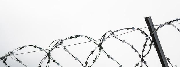Fil de fer barbelé à la frontière du pays. fil de fer barbelé pour interdiction Photo Premium
