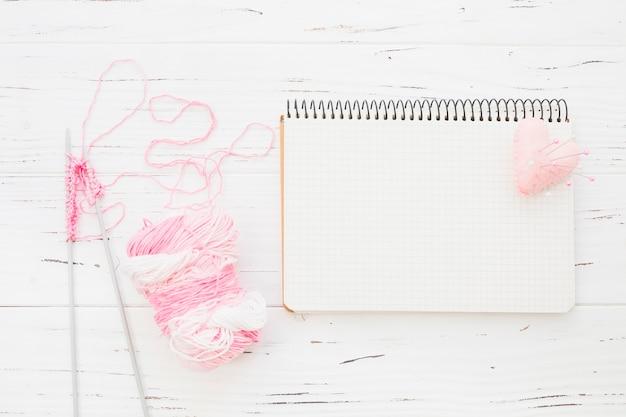 Fil rose avec crochet à côté du bloc-notes et coeur sur fond en bois Photo gratuit