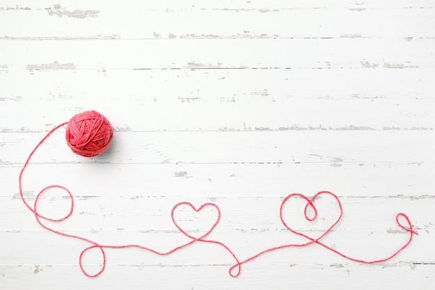 Fil rouge, deux coeurs et enchevêtrement sur bois clair Photo Premium