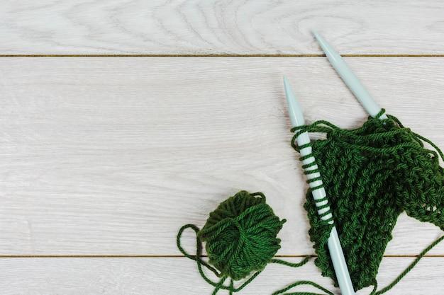 Fil vert crochetant et tricotant avec des aiguilles sur un fond en bois Photo gratuit