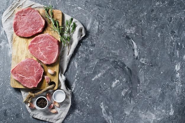 Filet de bifteck sur une planche à découper en bois, ail et un brin de romarin. Photo Premium